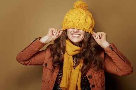 Hello autumn. Portrait of happy trendy woman in yellow scarf with beret over eyes against beige background.