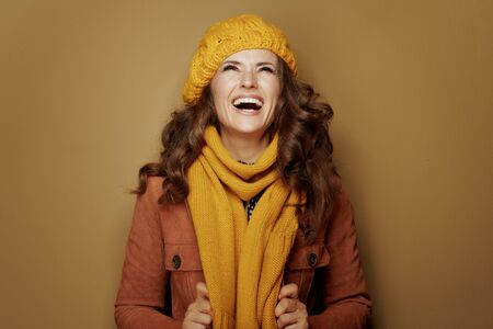 Hello autumn. smiling modern woman in yellow beret and scarf looking up on copy space isolated on beige background. Reklamní fotografie