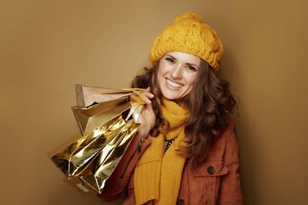 Hello autumn. Portrait of happy trendy woman in yellow beret and scarf with shopping bags isolated on bronze background.
