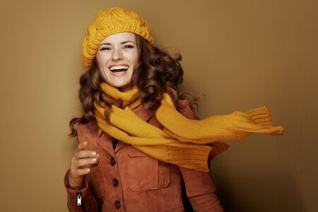 Hello autumn. Portrait of smiling trendy woman in yellow beret and scarf on bronze background.