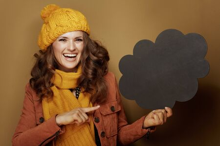 Hello autumn. Portrait of smiling modern woman in yellow beret and scarf pointing at cloud shape blank blackboard isolated on brown background. Reklamní fotografie