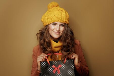 Hello autumn. Portrait of 40 year old woman in yellow beret and scarf with black dotted shopping bag on beige background.