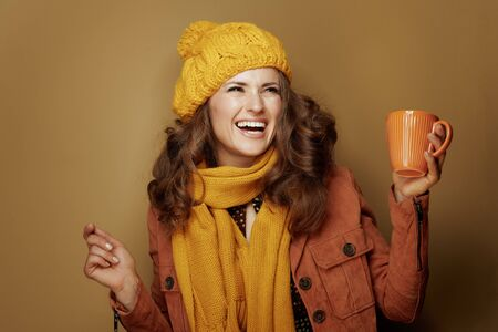 Hello autumn. happy modern woman in yellow beret and scarf with cup of pumpkin latte dancing isolated on beige.