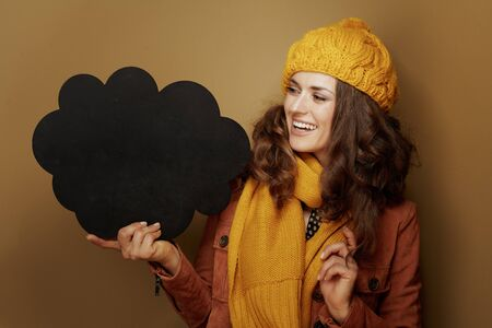 Hello autumn. smiling young woman in yellow beret and scarf looking at cloud shape blank blackboard on bronze background.