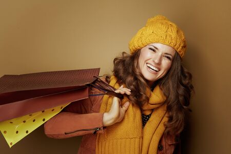 Hello autumn. Portrait of 40 year old woman in yellow beret and scarf with shopping bags against beige background.