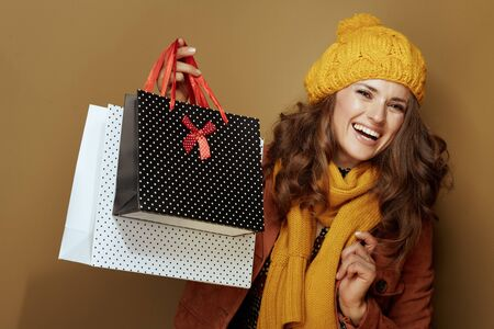 Hello autumn. Portrait of smiling modern woman in yellow beret and scarf showing shopping bags on bronze background.
