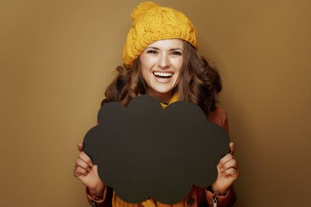 Hello autumn. Portrait of smiling trendy woman in yellow beret and scarf showing cloud shape blank blackboard isolated on brown background.