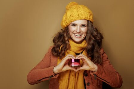 Hello autumn. Portrait of smiling stylish woman in yellow beret and scarf showing jar of facial creme with heart shaped hands isolated on bronze background.