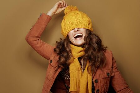Hello autumn. cheerful young woman in yellow scarf with beret over eyes on beige background.