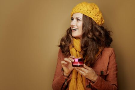 Hello autumn. Side view of smiling modern woman in yellow beret and scarf with jar of facial creme looking at copy space against bronze background. Reklamní fotografie