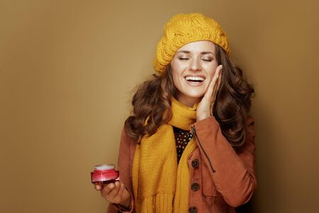 Hello autumn. Portrait of 40 year old woman in yellow beret and scarf with jar of facial creme satisfied with skin condition isolated on brown background. Reklamní fotografie