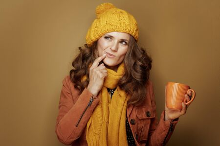 Hello autumn. Portrait of pensive modern woman in yellow beret and scarf with cup of soy latte isolated on beige background.