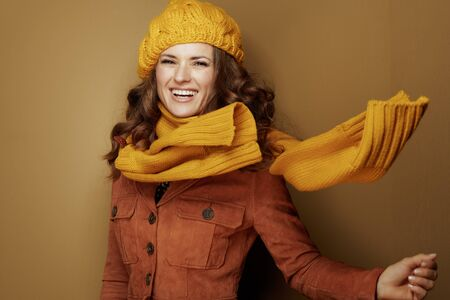 Hello autumn. Portrait of 40 year old woman in yellow beret and scarf on bronze background. Reklamní fotografie