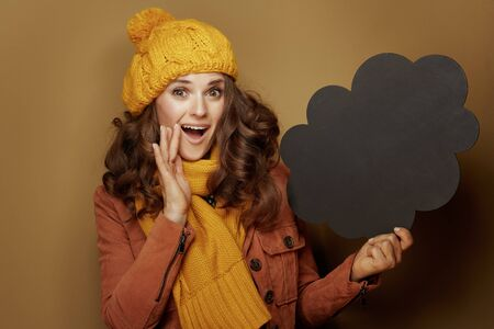 Hello autumn. Portrait of smiling elegant woman in yellow beret and scarf showing cloud shape blank blackboard and telling something exciting on beige background.