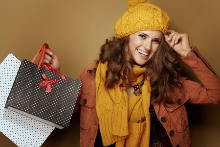 Hello autumn. Portrait of happy young woman in yellow beret and scarf with shopping bags on beige background.