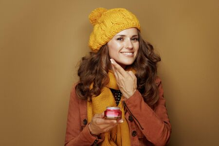 Hello autumn. Portrait of happy young woman in yellow beret and scarf using facial creme on brown background.