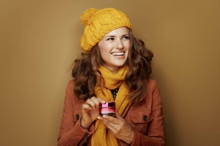 Hello autumn. smiling stylish woman in yellow beret and scarf with jar of facial creme looking at copy space against bronze background.