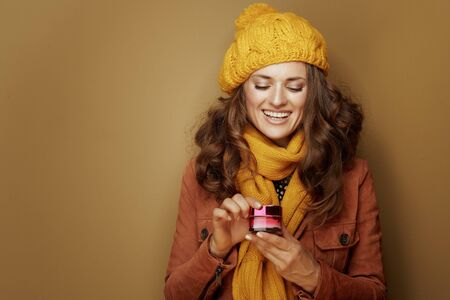Hello autumn. 40 year old woman in yellow beret and scarf opening jar of facial creme on bronze background. Reklamní fotografie