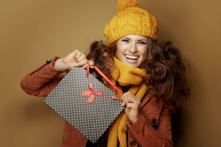 Hello autumn. Portrait of smiling young woman in yellow beret and scarf showing black dotted shopping bag against brown background. Reklamní fotografie