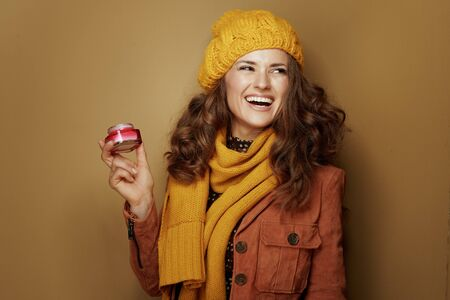 Hello autumn. smiling trendy woman in yellow beret and scarf with jar of facial creme looking at copy space isolated on beige background.