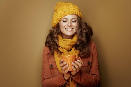 Hello autumn. relaxed young woman in yellow beret and scarf enjoying cup of pumpkin latte isolated on beige.