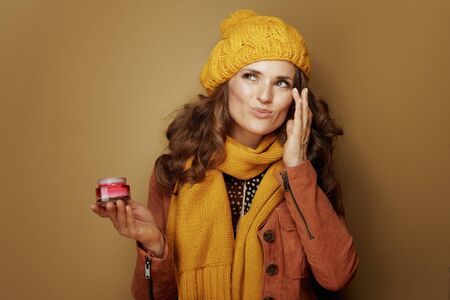 Hello autumn. modern woman in yellow beret and scarf using facial creme isolated on bronze background. Reklamní fotografie