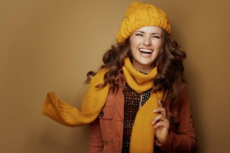 Hello autumn. Portrait of cheerful elegant woman in yellow beret and scarf isolated on brown background. Reklamní fotografie