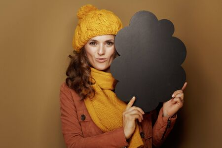 Hello autumn. Portrait of elegant woman in yellow beret and scarf showing cloud shape blank blackboard on beige background.