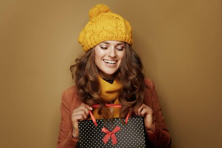 Hello autumn. Portrait of happy stylish woman in yellow beret and scarf with black dotted shopping bag on brown background.