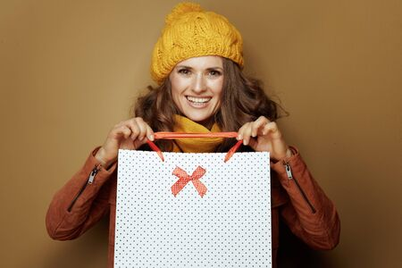 Hello autumn. Portrait of smiling modern woman in yellow beret and scarf showing shopping bags on beige background.