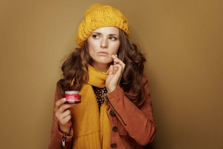 Hello autumn. Portrait of concerned 40 year old woman in yellow beret and scarf with jar of facial creme against beige background.