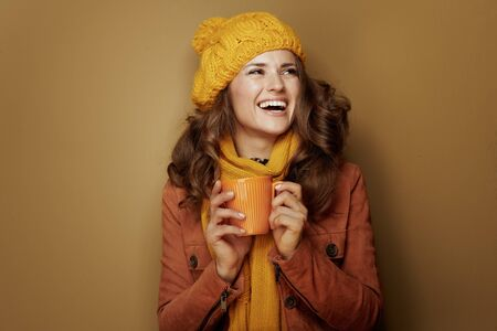 Hello autumn. happy elegant woman in yellow beret and scarf with cup of pumpkin latte isolated on brown background. Reklamní fotografie