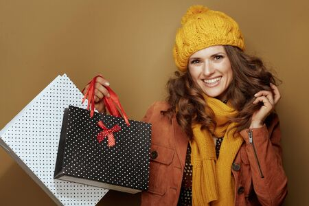 Hello autumn. Portrait of smiling trendy woman in yellow beret and scarf with shopping bags against brown background.