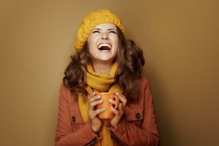 Hello autumn. smiling trendy woman in yellow beret and scarf with cup of hot chocolate looking up at copy space isolated on brown background.