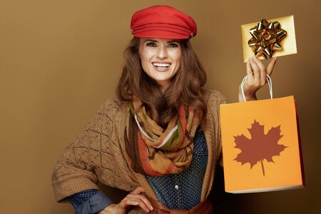 happy young woman in red cap, scarf, jeans shirt and cardigan showing autumn shopping bag and golden gift card isolated on bronze background. Stock Photo