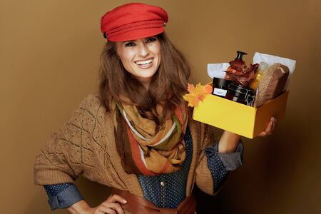 Portrait of smiling trendy woman in red cap, scarf, jeans shirt and cardigan showing autumn beauty cosmetics box isolated on bronze background.
