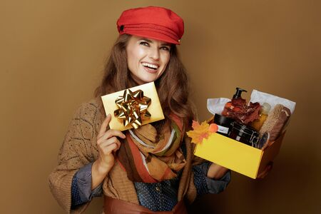 pensive stylish 40 year old woman in red cap, scarf, jeans shirt and cardigan showing autumn beauty cosmetics box and golden gift card against brown background.