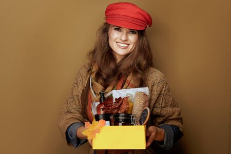 happy stylish middle age woman in red cap, scarf, jeans shirt and cardigan showing autumn beauty cosmetics box on brown background.