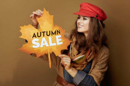 smiling stylish middle age woman in red cap, scarf, jeans shirt and cardigan looking at autumn sale banner against beige background.