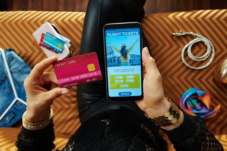 elegant housewife with credit card buying plane tickets online on a smartphone while sitting on couch in the modern living room.