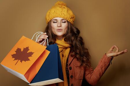 relaxed young woman in yellow beret and scarf with autumn shopping bags meditating isolated on beige background. Archivio Fotografico