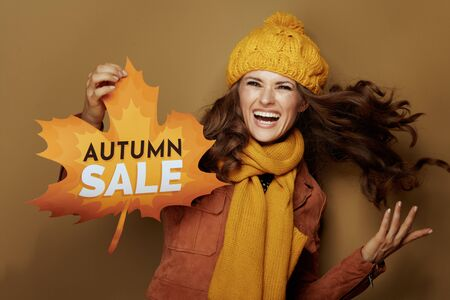 cheerful modern woman in yellow beret and scarf showing autumn sale banner isolated on brown background. Imagens