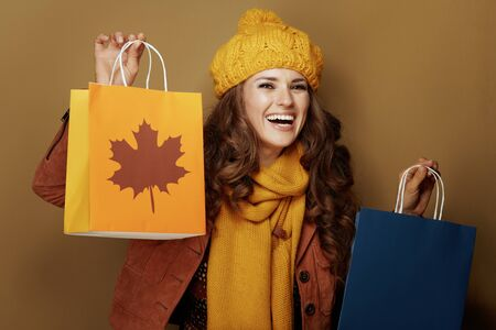 smiling young woman in yellow beret and scarf showing autumn shopping bags on brown background.
