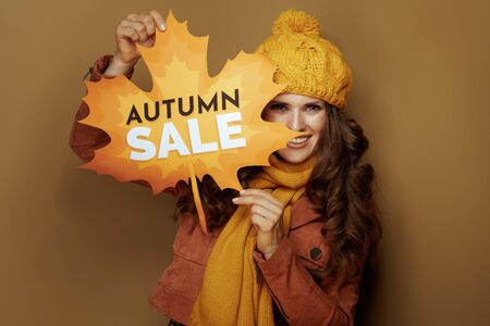 happy stylish woman in yellow beret and scarf showing autumn sale banner on beige background.