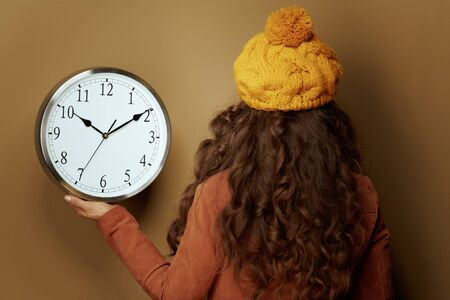 Seen from behind elegant woman in yellow beret and scarf showing round clock remind about autumn time change isolated on beige background.