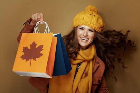 cheerful elegant woman in yellow beret and scarf showing autumn shopping bags on beige background.