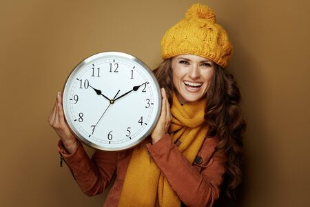 happy elegant woman in yellow beret and scarf showing round clock remind about autumn time change against brown background.
