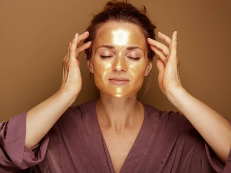 Portrait of modern 40 year old woman with golden cosmetic face mask making facial self massage isolated on brown background.