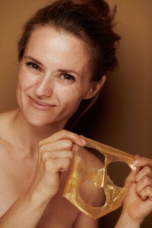 Portrait of smiling young woman showing freshly removed from face golden cosmetic mask isolated on brown background.