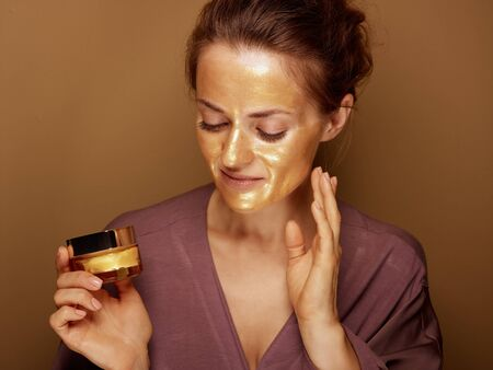 Portrait of happy young housewife with golden cosmetic face mask holding bottle of facial creme isolated on bronze background. Stock Photo